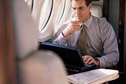 Business executive with laptop on airplane