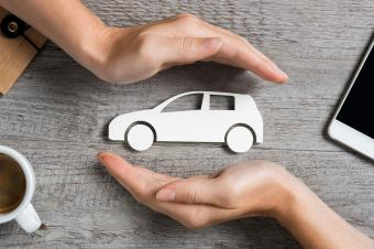 Hands protecting icon of car