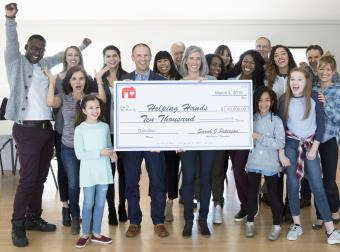 Enthusiastic community with large donation check